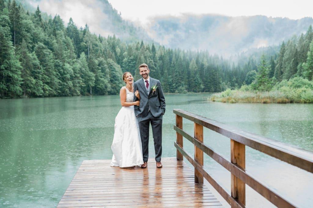 stilvolle elegante und zeitlose Hochzeitsfotos am See in den Bergen. Das Brautpaar steht bei Regen vor einem See und den Bergen im Nebel und lachen der Hochzeitsfotografin zu. Die Braut trägt ein weißes Brautkleid und der Bräutigam trägt einen eleganten dunkelgrauen Anzug