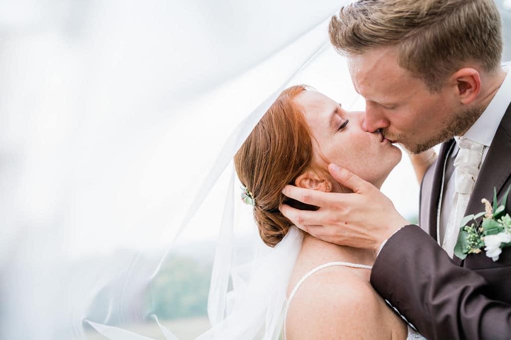 """Das Hochzeitsfoto zeigt eine Braut mit langem Schleier. Sie küsst ihren Bräutigam, der einen braunen Anzug trägt. Was Brautpaare sagen: """"Astrid weiß genau, wann sie wo sein muss und fängt somit jedes Detail und jeden Moment rechtzeitig ein. 100% Weiterempfehlung"""