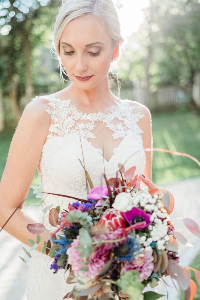 Hochzeitsfoto einer eleganten Braut mit mondernem Blumenstrauß bei Sonnenuntergang