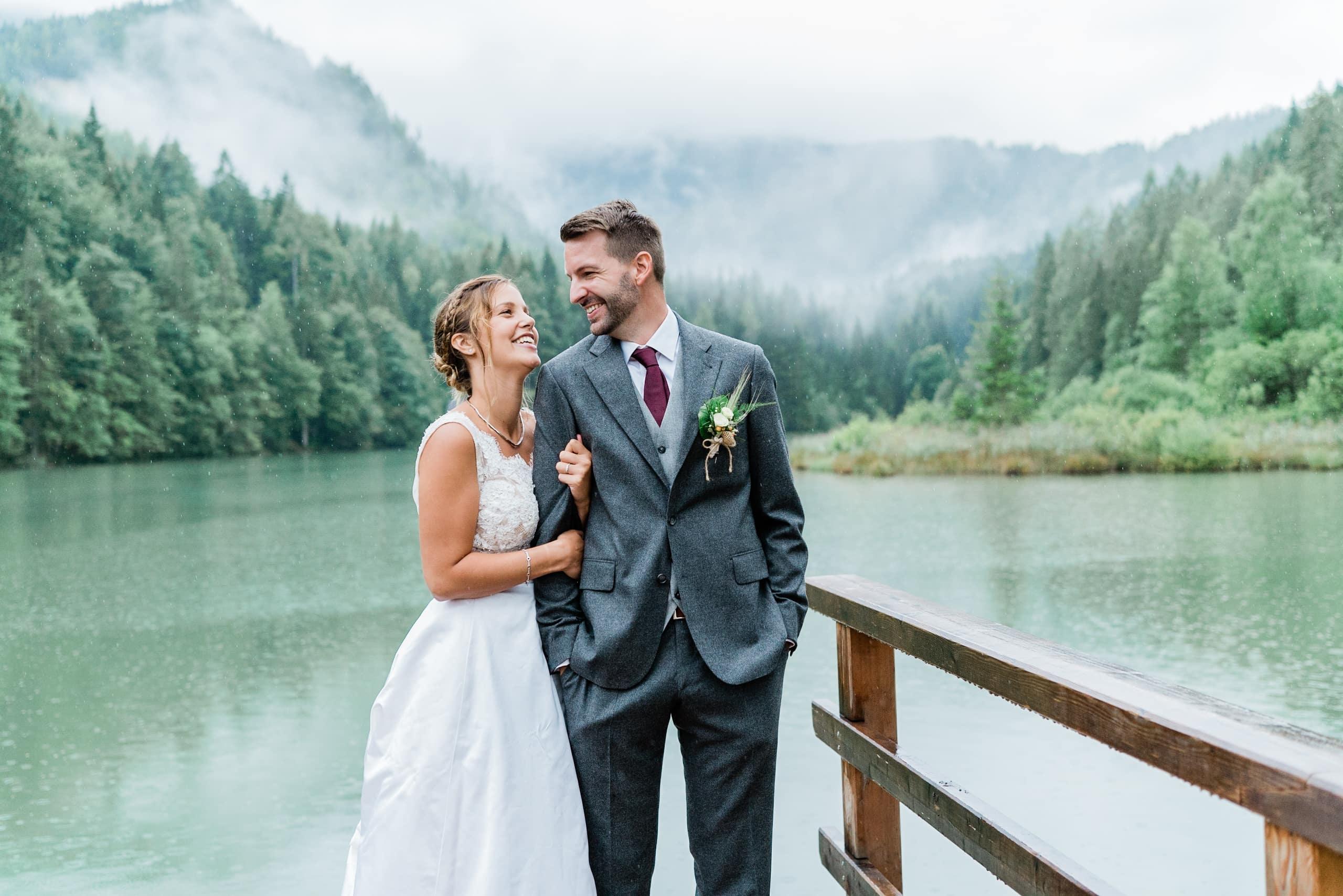 stilvolle elegante und zeitlose Hochzeitsfotos am See in den Bergen. Das Brautpaar steht bei Regen vor einem See und den Bergen im Nebel und lacht sich an. Die Braut trägt ein weißes Brautkleid und der Bräutigam trägt einen eleganten dunkelgrauen Anzug
