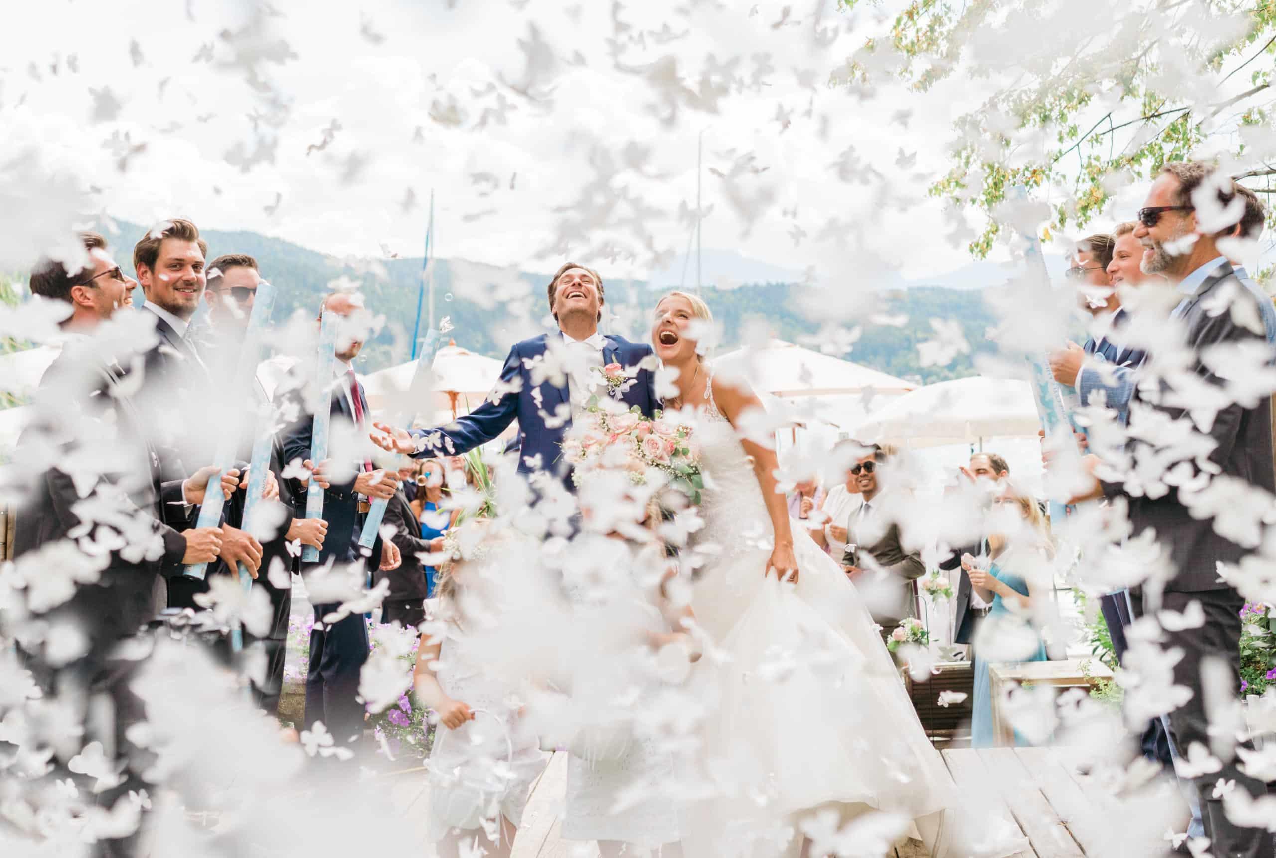 Stilvolles und elegantes Hochzeitsfoto am See. Frisch verheiratetes Brautpaar feiert am See ihre Hochzeit. Die Braut trägt ein weißes HOchzeitskleid. Der Bräutigam einen dunkelblauen eleganten Anzug